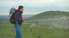Guy taking off heavy rucksack, breathing fresh air, enjoying amazing landscape Stock Footage