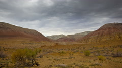 Timelapse of clouds above desert and colored hills Stock Footage