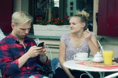 Girl eating mousse from coffee and boy using smartphone in the cafe Stock Footage