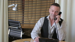 Handsome businessman talking on the phone in his office Stock Footage