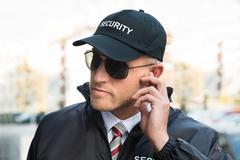 Portrait Of Young Male Security Guard Listening To Earpiece - stock photo