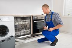 Young Handyman Looking At Dishwasher And Writing On Clipboard Stock Photos