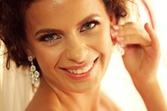Gorgeous bride putting her ear rings on - stock photo