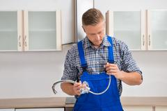 Young Male Plumber Holding Faucet In The Kitchen Room - stock photo