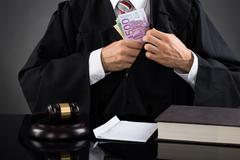 Close-up Of Male Judge Hiding Banknote At Desk Stock Photos