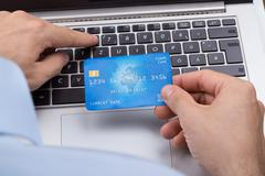 Close-up Of Person With Credit Card Shopping Online On Laptop - stock photo