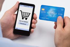 Close-up Of Person Shopping Online With Credit Card On Mobile Phone Stock Photos