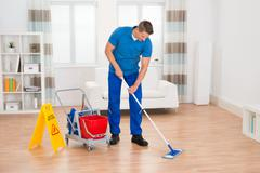 Stock Photo of Happy Worker With Cleaning Equipments And Wet Floor Sign In House