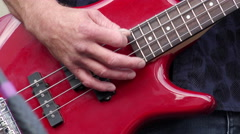 Detail of a musician playing a red electric bass guitar. Arkistovideo