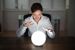 Young Businesswoman Looking Into The Future In A Crystal Ball In Office Stock Photos