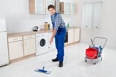 Young Happy Worker In Overall Mopping Floor Stock Photos