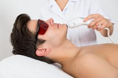 Young Man Receiving Laser Hair Removal Treatment At Beauty Center Stock Photos
