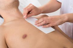 Close-up Of Person Hands Waxing Man's Chest With Wax Strip - stock photo
