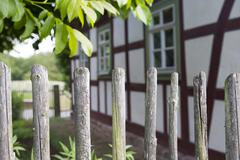 Wooden fence in front of an old house Stock Photos