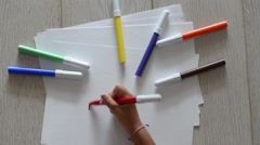 Young girl draws 3 hearts on a white sheet with a red marker Stock Footage