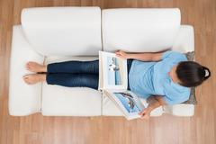 High Angle View Of Young Woman Looking At Photo Album On Sofa Stock Photos