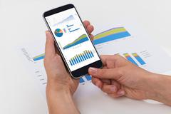 Close-up Of Person Hands Analyzing Graphs On Mobile Phone Display Stock Photos