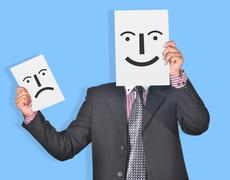 Professional with Happy & Sad face smiles in hands - stock photo