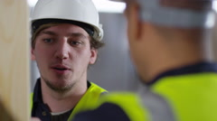 4k Male construction worker or tradesman working with male apprentice - stock footage
