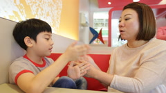 Happy asian mother and son are playing clap in hands together - stock footage