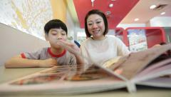 Asian cute boy with mother reading menu book and point .Happy face Stock Footage