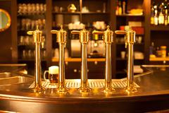Luxury gold beer spigot at the brewery with a glass of beer - stock photo