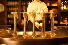 waiter is drafting a beer from a golden spigot - stock photo