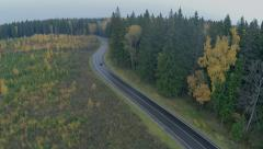 Stock Video Footage of Car driving through the forest road. Aerial shot