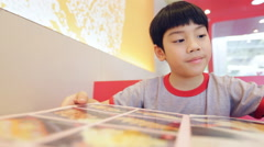 Asian cute boy reading menu book and point .Happy face Stock Footage