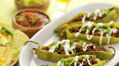 Chipotle beef & bean stuffed chili peppers garnished with sour cream and scallio Stock Footage