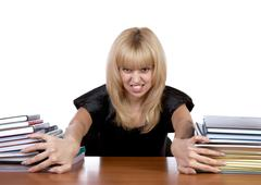 The expressional girl moves apart piles of papers - stock photo