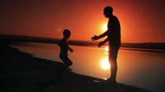Father and son playing on the beach at sunset time. The concept of close-knit Stock Footage