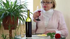 Woman sits at a table drinking red wine and eating cheese Stock Footage