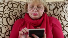 Woman sitting on a couch and using electronic book. Woman with e-book Stock Footage