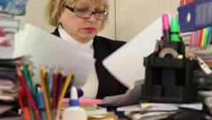Woman as an administration economist in glasses tears commercial papers Stock Footage