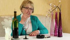 Woman drinking wine and smoking a cigarette Stock Footage