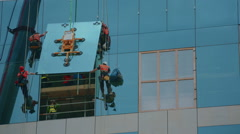 Wide shot of group of builders securing a glass panel in place Stock Footage