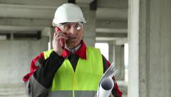 Manager of the works with red smartphone on the construction site Stock Footage