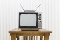 Old Portable Television with Antenna on Wood Table - stock photo