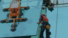 Close-up shot of group of builders securing a glass panel in place Stock Footage