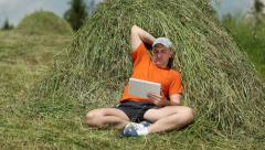 Man in orange t-shirt with tablet PC sits near a haystack Stock Footage
