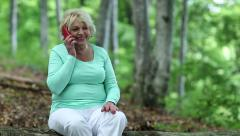 Woman sits on a fallen tree in the forest and communicates via smartphone Stock Footage