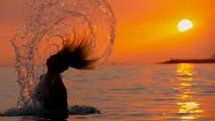 Woman comes out from water splashing her hair backward slow motion Stock Footage