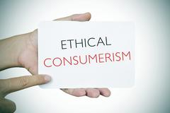 man with a signboard with the text ethical consumerism, vignetted - stock photo