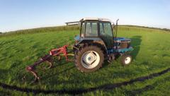 Aerial of stunt drone flying very close proximity to a parked blue tractor 4k Stock Footage