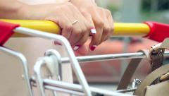 Woman  hands takeing shopping cart at street Stock Footage