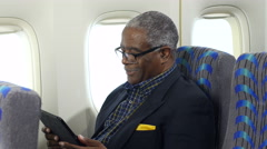 Older black male using a tablet/ipad on an airplane Stock Footage