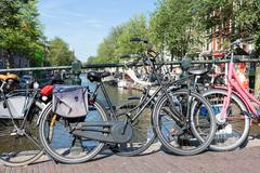 Bicycles at a bridge over an Amsterdam canal Stock Photos