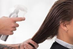 Cheerful young hairstylist is serving his client Stock Photos