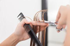Skilled young hairstylist is making a haircut to her customer - stock photo